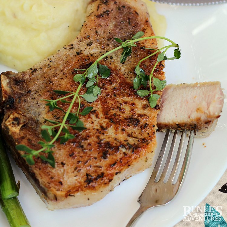 Close up of browned sous vide pork chop with thyme on it and a piece cut off ready to eat
