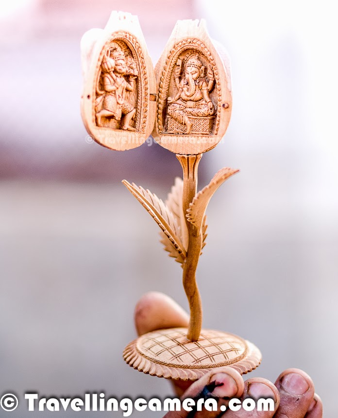 Wood carving using special wood like sandal, sheesham and rosewood is done to create some beautiful handicraft items showing symbols of rich Indian cultural heritage. This is one of the old art-form in India and done is few of the states like Rajasthan. You must have seen wood-carved elephants, peacocks and other cultural symbols in various handicraft shops across the country, but lot more than that is created by Wood-carving artsists for special clients, museums and some exclusive art-galleries. During our recent trip to Churu, we met a family of artists who have been doing this for many years now and various memebers of the family have got national awards for creating some exceptional art-pieces of wood-carving. This family has some records in Limca book as well. This was a great rendezvous, which exposed us to another great art-form of India. While we were roaming around Churu streets full of old Havelis, we realized that every haveli had beautiful wooden doors carved with beautiful designs on them and most of the furniture, windows and chattris were wood-carved. All this shows that how important this art would have been in old times as well. Most of the palaces and forts across the country have rich wood-carved art-pieces. Another great example comes to my mind is - Indian Institute of Advanced studies in Shimla which is Viceregal Lodge. I am sure that India must have many families doing this work in old days, but not very sure how this art-form is performing these days and how much demand we have. Maintaining these art-pieces is very challenging and everybody may not be able to afford good wood-carved art-pieces. Here I am not talking about the smaller elephants & peacocks.Here is the family of Wood-Carving artists. Don't be surprised if I say that the little boy also does carving, although his father says that he wastes lot of wood as of now :). But still taking such lovely art form further is a big thing and I really salute such families in India who are preserving these important art for next generations. Wood carving art is shown as xyloglyphy. The artists carve design on wood by hand with some sharp carving tools as you can see in the photograph on left. It is a traditional art which is extremely popular in India and abrpoad. This family has made so many wooden souvenirs which are in a great demand in Delhi as well as some specific families abroad. They usually give these art-works to gallerys, 5 star hotels and handicraft emporiums in Delhi to sell and also get direct orders from existing clients who are different parts of the world now. Rajasthan is one of the renowned states of India for its excellence in wood carving. Churu has few more families like this but this one is very special which is recognized by state and center government for many years. Different generations of this family has got national awards for wood-carving art. Rajasthan has high number of people involved in wood carving.This family uses sandal wood to create some marvelous art pieces by craving very intricate designs on them. This Photo Journey has one of the beautiful example to share. The art-forms made of sandalwood are the most famous among the other wooden artifacts for its sweet fragrance and it seems that sandalwood is most appropriate for intricate carving. At the same time, sandalwood art-pieces are most expensive amongst the all. Apart from states like Rajasthan, Mysore, Tirupati, Madurai, Coimbatore in Tamilnadu, Delhi and Varanasi are few of the main areas to find wood-carving artists in India. btw, Sandal is known as 'chandan' in HindiThe tiny instruments used for sandalwood carving are extremely simple.Things like a saw, plane, mallet hone or fine-grained hard stone, an assortment of various shapes and sizes of chisels and a few engraving tools, which were very delicate. The photograph on the left shows a box in the bottom with all tiny tools used for wood carving. Also a closer look of these tools is shared in very first photograph of this Photo Journey. First a design is made on wood with pencil, at times paper is pasted to ensure that wood color is intact after the project is over. Then a basic outline is made with one of the carving equipments. Slowing this outline becomes the basic carved design and then starts the real art of making each corner of the design elegant to look as a masterpiece. Last finishing steps is to ensure the perfectness and light/shade patterns, appropriate curves and textureAbove photograph shows a flower carved out of a sandalwood piece. Isn't it amazing. But hold on, this one is very basic as per there artists. btw, the upper part can be collapsed and it looks like a rose.  The most popular articles carved out of sandal wood are  elephants, peacocks, square figures and rectangular boxes to keep jewellery, photo frames, key chains and chess sets etc. These are few which are easily accessible in handicraft shops in different cities of India.Let me share some details about this amazing art-work created by this family. This is a creation to simulate the pocket clock with a string. The above photograph shows the clock with a wooden string. Here notice the designs carved out of this sandalwood piece and one thing which I want to highlight that  - this whole creation is made out of single sandal-wood piece without any joints which is brilliant. Before I say further, you may have guesses things from the other photographs shown on both sides. Two parts of the clock can come out and inside them, we have few more creations. On one side, when we open it, we see Tajmahal. Story doesn't end here. There is another creation under the Tajmahal. When we unfold it, there is a a grave under it as we have in real Tajmahal. Again this grave could be opened to see the body. Please see the photograph below to have a closer look. This was very tiny. Can you imagine the way this whole creation would have been made. As per artist, this creation took 5 months to complete or may be more. He showed us many of such creations.Wood carving in Rajasthan and other states of India is one of the important art form. And it was great to know that state government and Govt of India recognize these folks for their great work. While compiling this Photo Journey, I came a across a link which is listing various national awards for artists of Rajasthan - http://www.jawaharkalakendra.rajasthan.gov.in/nationallist.htm . & http://www.rajsico.gov.in/Artisan.html Unfortunately I lost my diary which had more details about this family but hope to get in touch with them soon to share specific details about this family of Sandal Wood Carving Artists from Churu. We are looking for more such families who are indulged in some form of art for generations. So please keep us updated, in case you know someone.