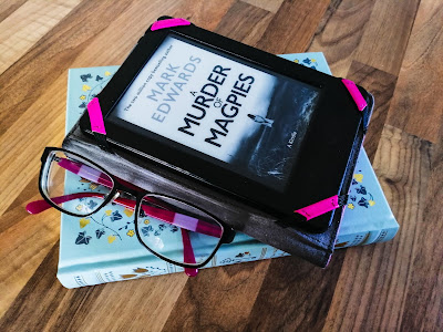 Pile of books and Kindle with glasses