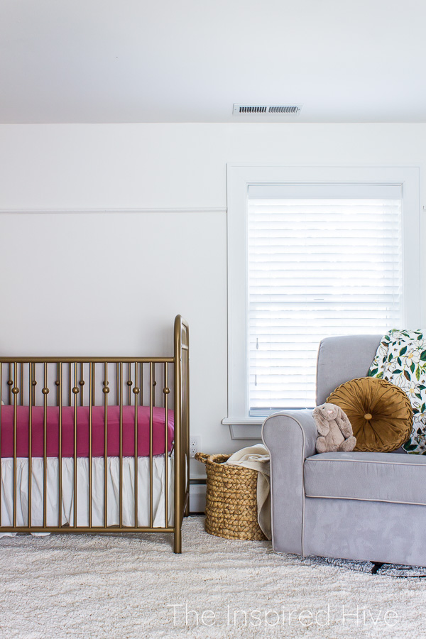 Gold crib with pink sheets and grey chair in girl's nursery