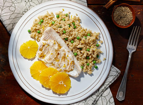 Moroccan-spiced fish and couscous and orange slices in a serving dish