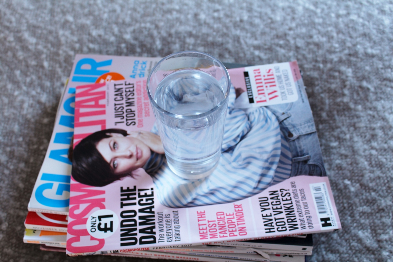 Glass of water on pile of magazines