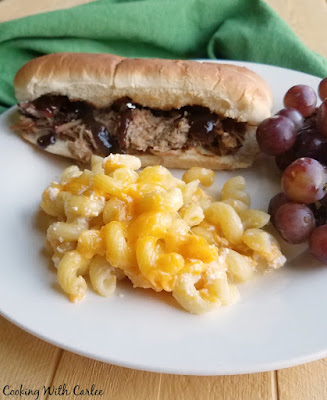 macaroni and cheese on plate with pulled pork sandwich and grapes