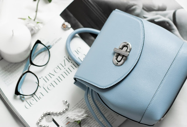 small blue handbag on top of a magazine with a pair of glasses
