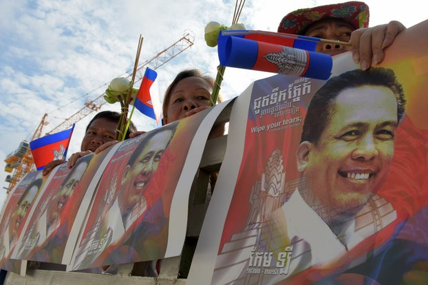 Cambodians hold images of Kem Ley, a Cambodian political analyst who was shot dead in broad daylight on July 10, during a funeral procession for him in Phnom Penh, July 24, 2016. AFP