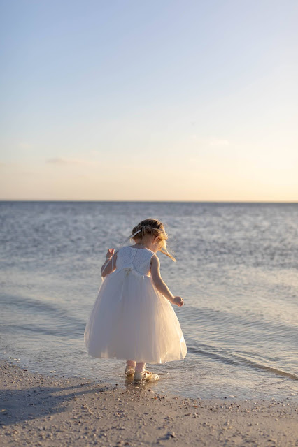 Unposed flower girl playing in the sand during sunset.