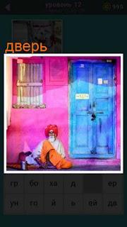 около двери голубого цвета сидит пожилой человек в тюрбане на голове