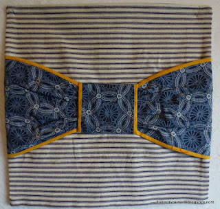 A large blue print bow edged with mustard is centered on blue and white mattress ticking.