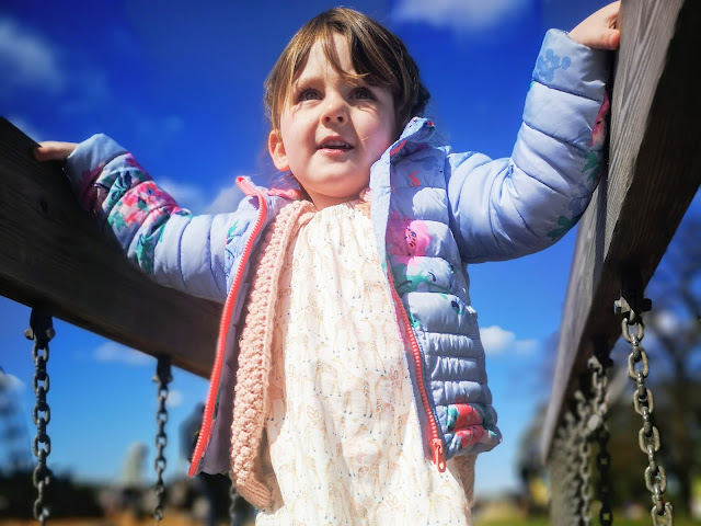 Image of a 3 yer old girl walking over a wobbly bridge in a play area. Wearing child joules floral coat, hand knitted pink cardigan and giraffe print dress. Hair in french braids. Taken at Yorkshire Wildlife Park