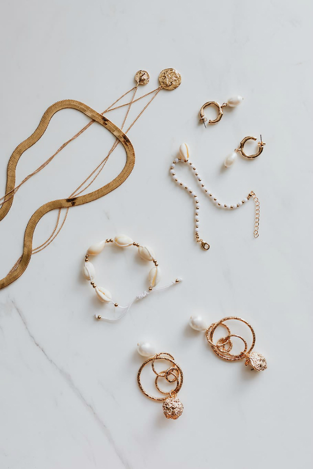 a flatlay showing gold jewellery pieces