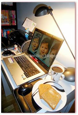 Imagem de um notebook ligado, ladeado de uma caneca de café e um prato duas fatias de pão integral com manteiga