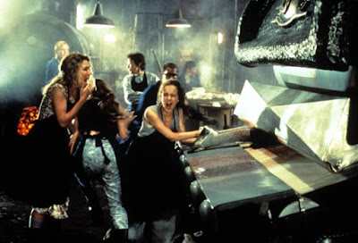 Several women stand around a defective machine screaming after it ate their coworkers in a movie still for Tobe Hooper's 1995 horror film The Mangler