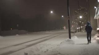 Μοναχικός άντρας περπατάει σε χιονισμένο δρόμο.