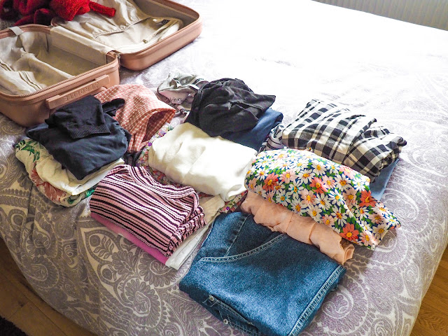 Different kind of clothes such as t shirts, jumpers on the bed next to my pink suitcase