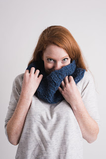 A woman wearing a dark blue worsted/aran weight cowl. She is holding it just over the bottom of her face.