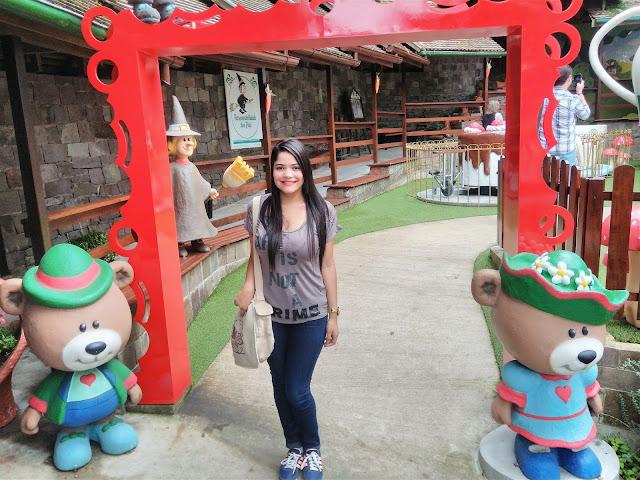 entrada de parque de miniatura com fachada vermelha e dois bonecos em formato de urso