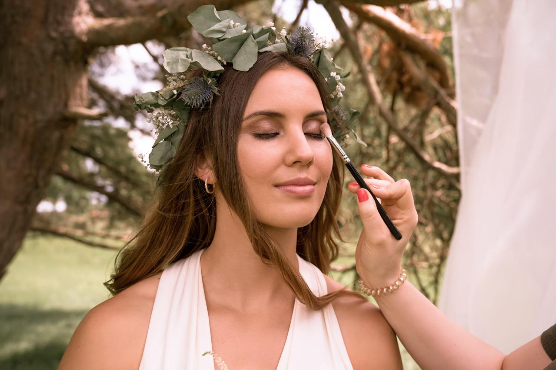 makeup artist applies makeup on a bride in the field