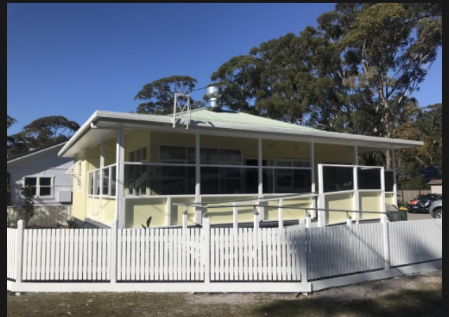 A corner view of the home. It is now painted yellow with white trim and white picket fence.  The front porch has been closed in with windows and a ramp has been added for access. The roof is now a silver grey.