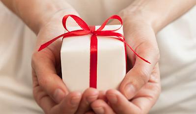يد تحمل هدية صغيرة برباط أحمر
