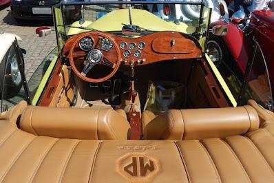 Estofamento em tom caramelo com painel e volante de madeira ante o capô amarelado: cores quentes para um conversível tropical.