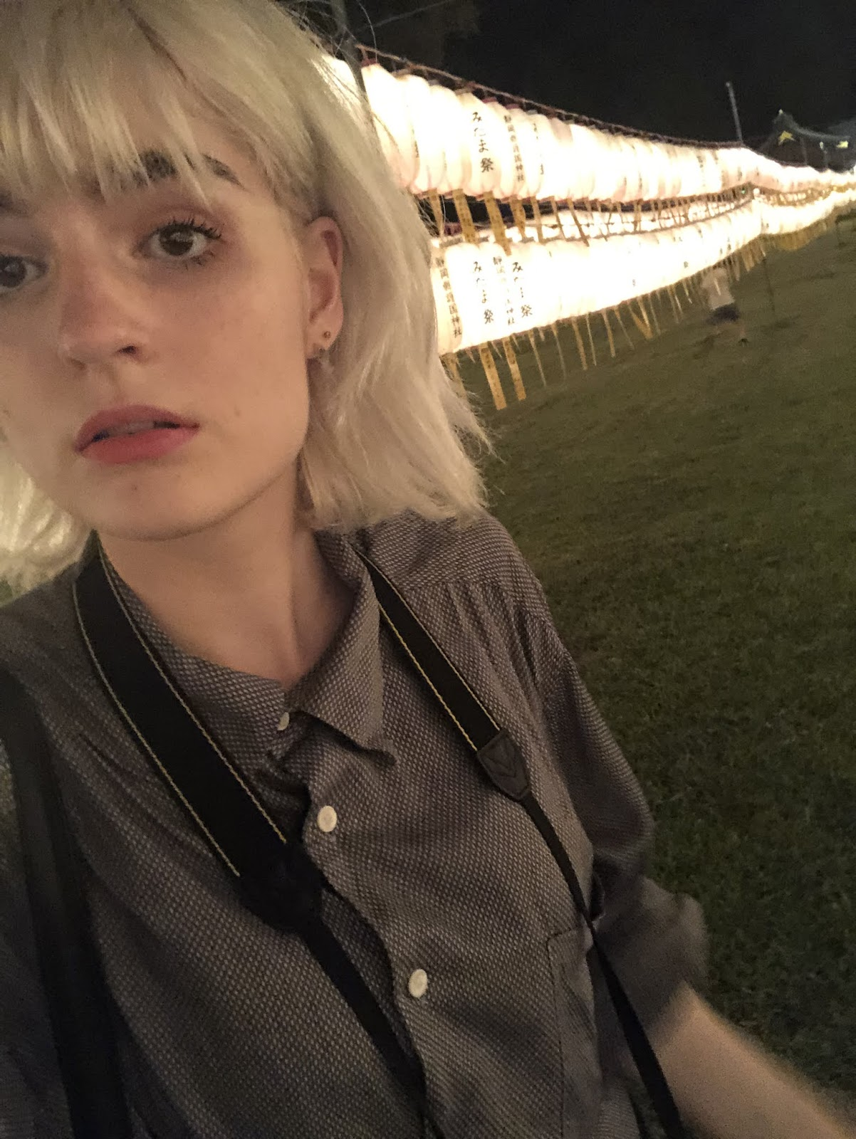 Girl with bleached silver hair in front of shrine lanterns