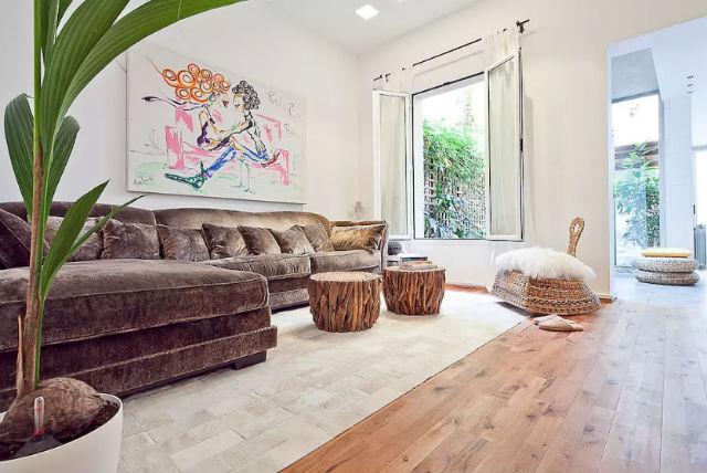 salón con sofá grande con chaiselongue de terciopelo marrón