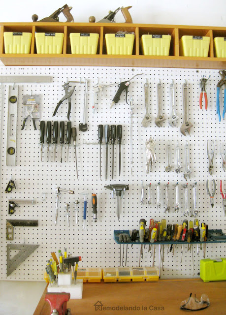 pegboard full of tools in the garage above bench with screwdrivers and containers