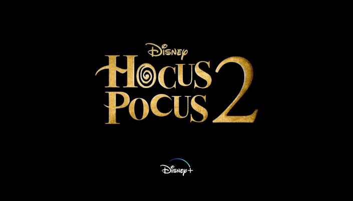 """""""Hocus Pocus 2"""" escrito em dourado numa fonte mais lúdica e com movimento, a primeira letra """"O"""" tem um espiral dentro. O fundo é preto e na base tem a logo do Disney plus."""