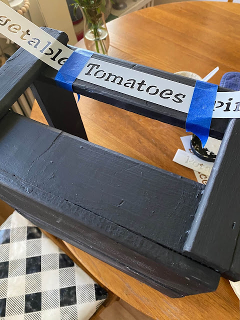 Photo of painted crate with tomato stencil taped to it