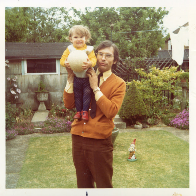 1970s Dads - the original hipsters. Dad in an orange sweater hold up his daughter. The New Dad. marchmatron.com9