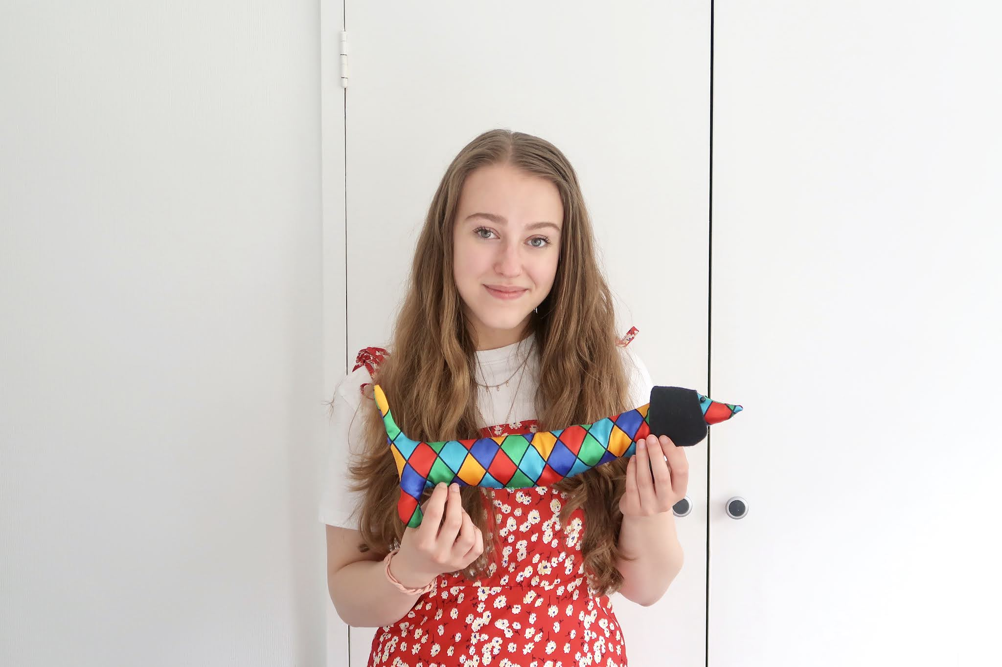 Georgie wearing a red floral dress holding up her latest sewing creation, a harlequin sausage dog wrist support for computers