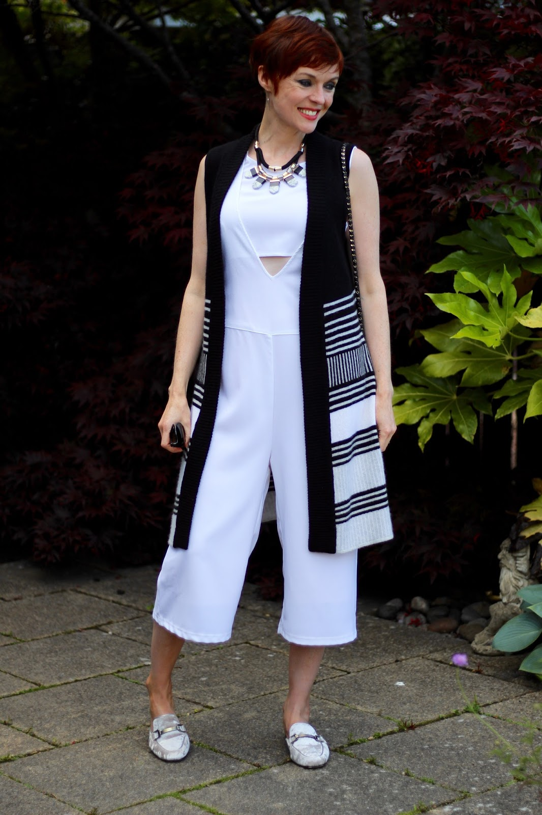White Jumpsuit, sleeveless black & White cardigan, silver backless loafers | Work look | Fake Fabulous
