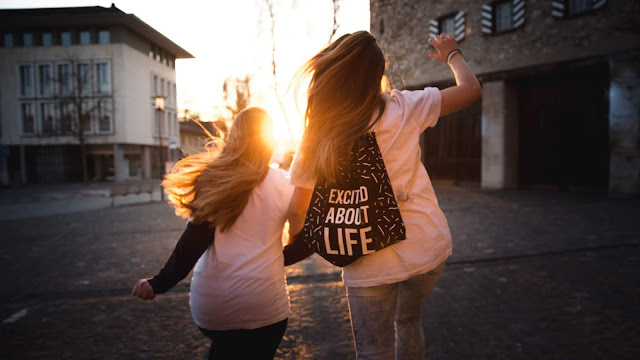 """2 girls running on a street facing the sun with one having a backpack which says,""""Excited for life"""""""