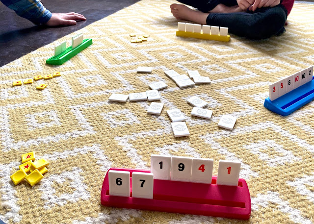 Racks, pieces and star counters on a rug as four people play rummikub junior to help bond and have fun as a family