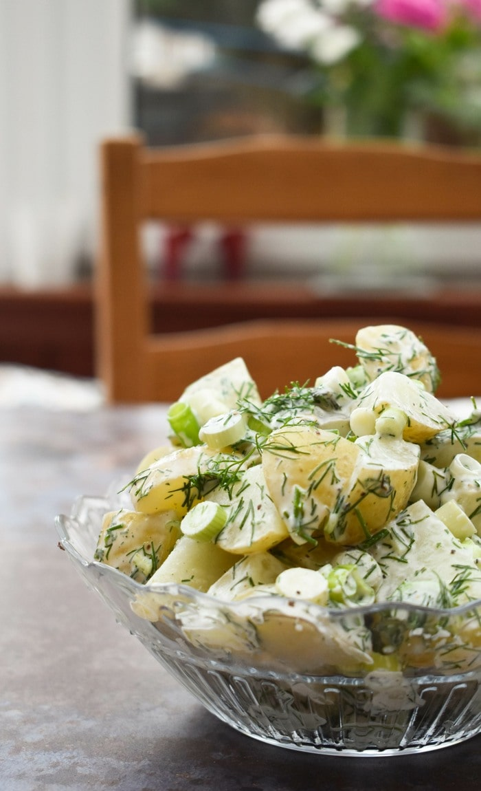 Potato salad with dill and spring onion in a patterned glass bowl on a wooden table