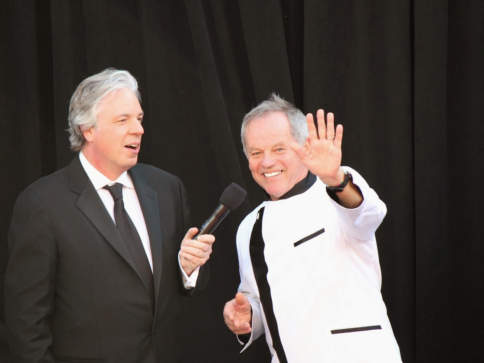 Chris Connelly interviewing Wolfgang Puck, who's waving to the fans, on the red carpet for the 2013 Oscars.
