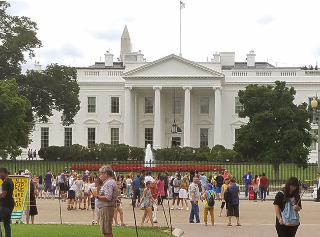 Pennsylvania Avenue view of the White House with people in front of it.