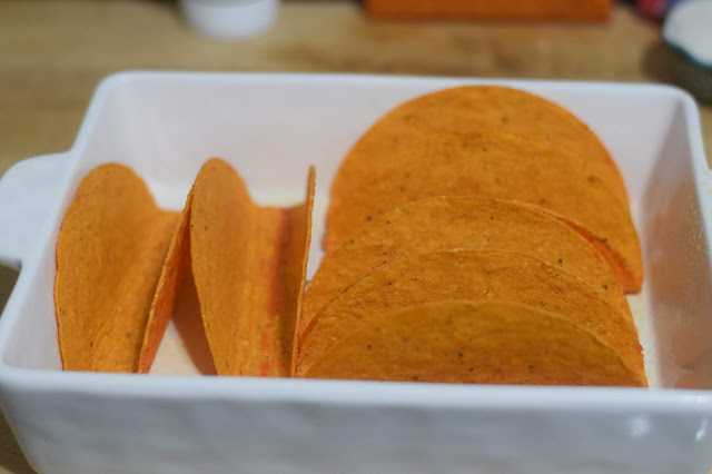 The flat bottom nacho cheese taco shells in a baking dish.
