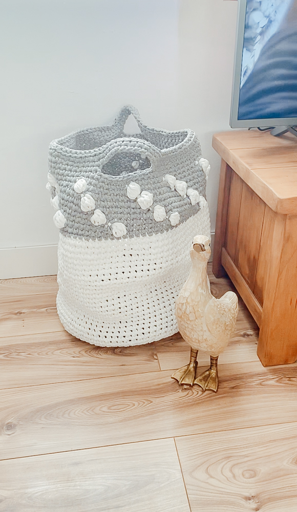 A crocheted grey and white storage basket