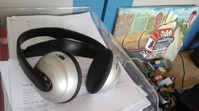 Koptelefoon op stapel papierbakjes met schilderij van vrachtwagen en papieren Minecraft bouwblokjes ernaast.