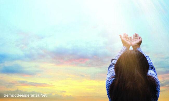 Mujer levantando las manos al cielo