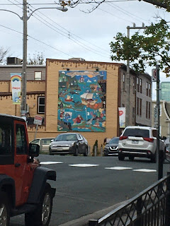 """Side of a two story building. The top edge of the building looks as if hot fudge were dripping down. Below the """"drips"""" is a mural depicting chocolate characters boating along a river. There are several cars visible reminding everyone that Duckworth Street is a very busy throughfare."""