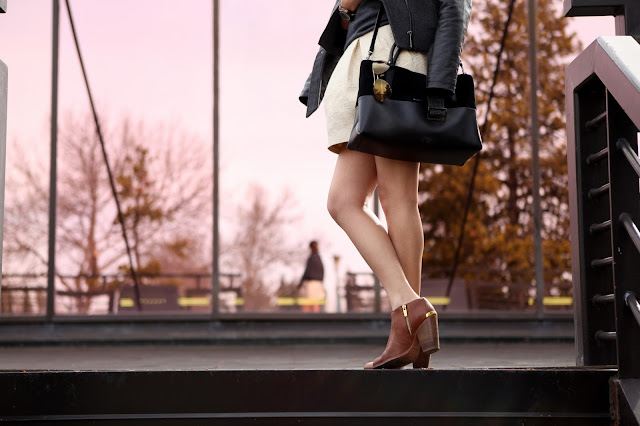 Cream and gold mini skirt and black coach bag