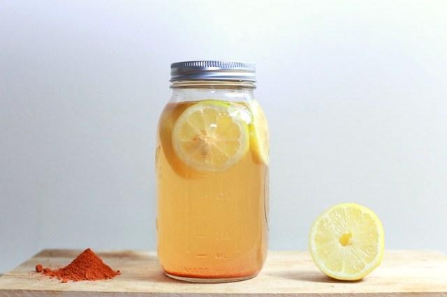 vaso de zumo con limón en rodajas y cayena