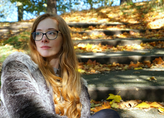 autumn photo of redhead wearing glasses and sitting outside on stone steps looking off camera