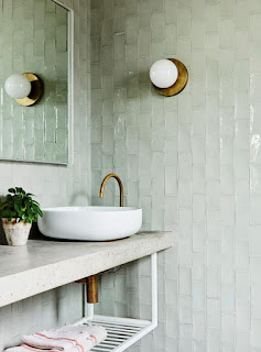 pale green shiny subway tiles in bathroom with white modern countertop and white milk glass wall sconce