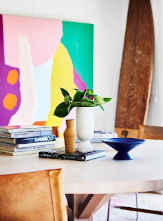 collection of geometric vases on dining table, wood surfboard, bright art