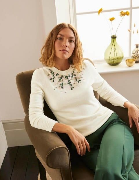 woman sitting in a chair wearing a white sweater embellished with crystals