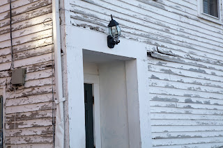 Crooked lamp on a house with peeling paint, in downtown Portsmouth, New Hampshire