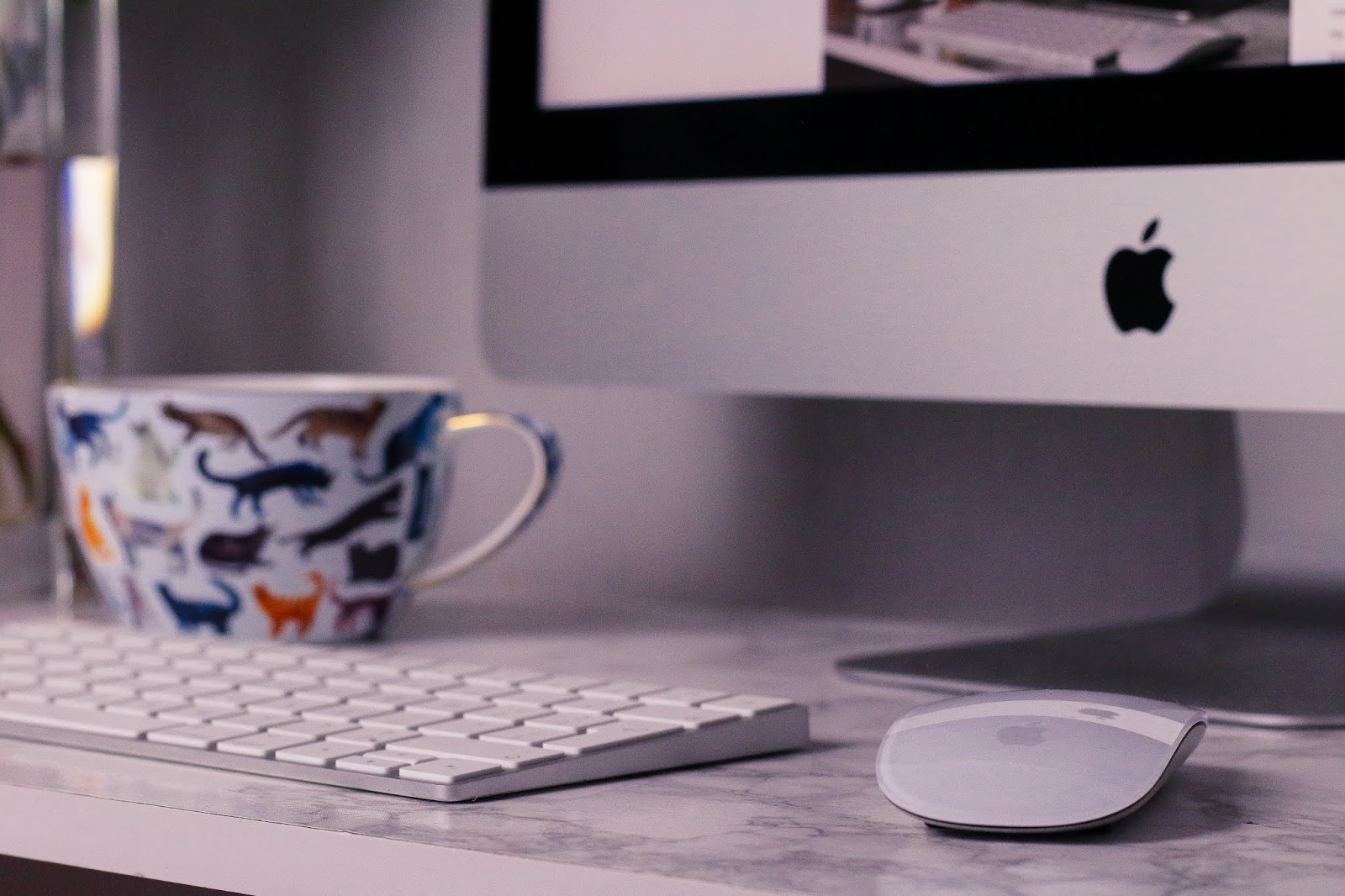 Close up of iMac sitting on a white marble desk with a cat cup next to it on thelifeofaglasgowgirl.co.uk